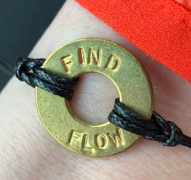 "Flat gold ring with an imprint: ""FIND FLOW"""